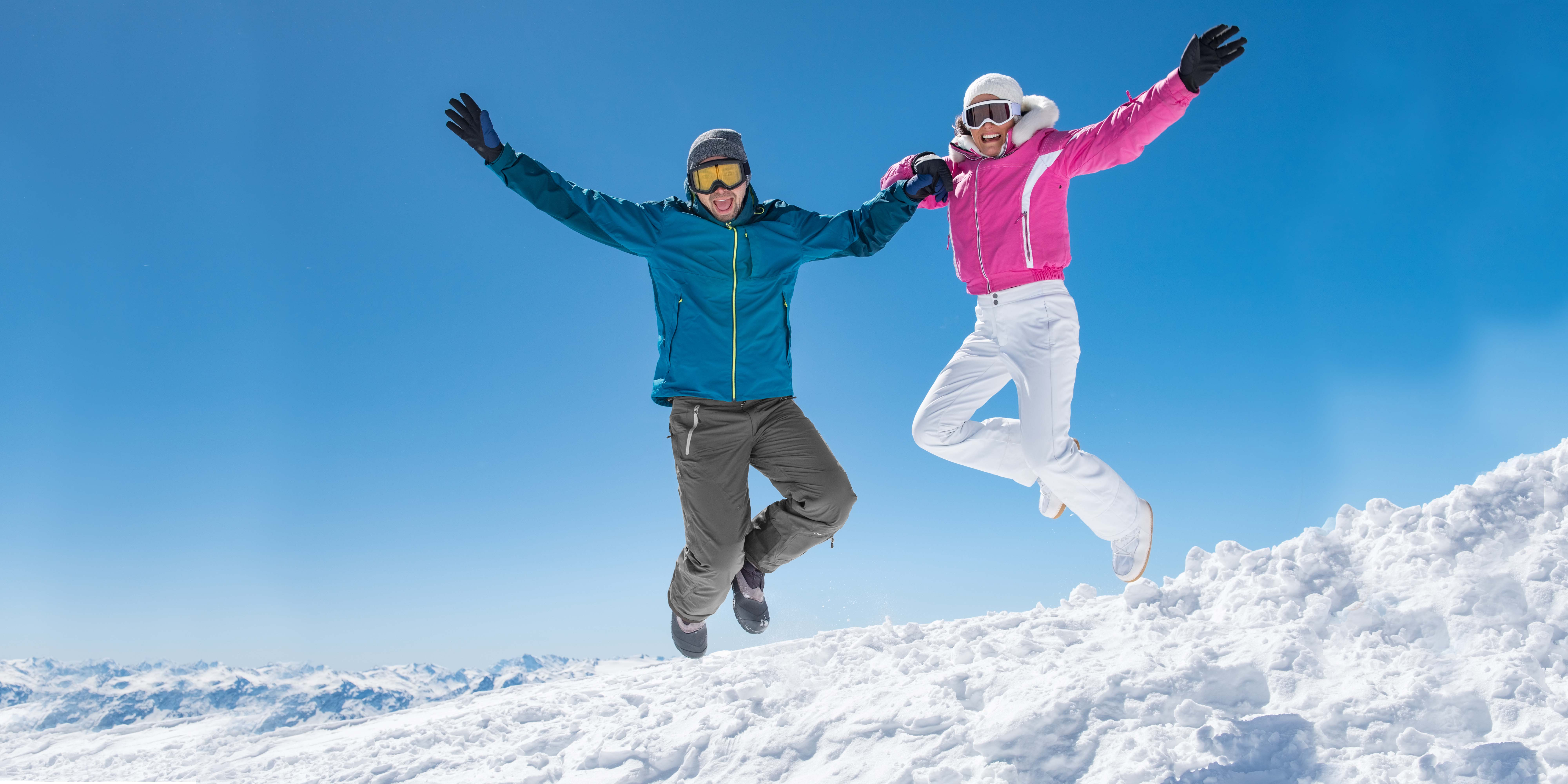 pareja salta sobre la nieve celebrando el inicio de la temporada de esqui